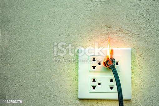 istock On fire electric wire plug Receptacle wall partition,Electric short circuit failure resulting in electricity wire burnt 1135799278