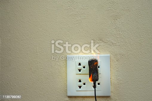 istock On fire electric wire plug Receptacle wall partition,Electric short circuit failure resulting in electricity wire burnt 1135799282