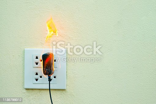 istock On fire electric wire plug Receptacle wall partition,Electric short circuit failure resulting in electricity wire burnt 1135799312