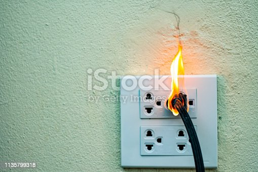 istock On fire electric wire plug Receptacle wall partition,Electric short circuit failure resulting in electricity wire burnt 1135799318