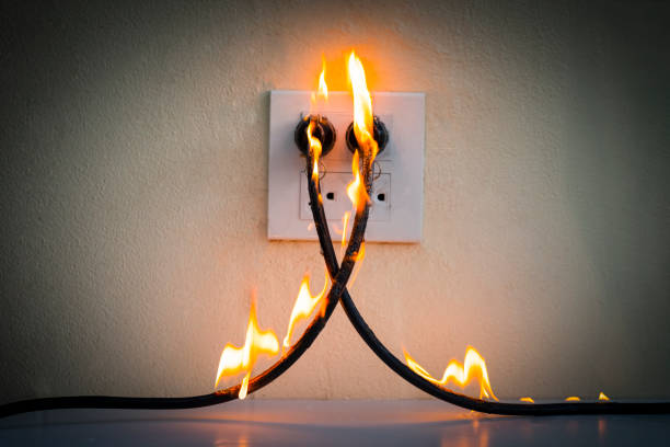 on fire electric wire plug receptacle wall partition,electric short circuit failure resulting in electricity wire burnt - fuoco foto e immagini stock