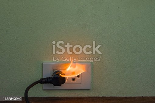 istock On fire electric wire plug Receptacle wall partition,Electric short circuit failure resulting in electricity wire burnt 1152840940