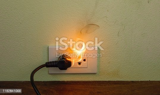 istock On fire electric wire plug Receptacle wall partition,Electric short circuit failure resulting in electricity wire burnt 1152841000