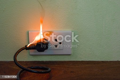 istock On fire electric wire plug Receptacle wall partition,Electric short circuit failure resulting in electricity wire burnt 1152841004
