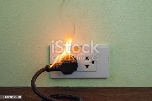 istock On fire electric wire plug Receptacle wall partition,Electric short circuit failure resulting in electricity wire burnt 1152841018