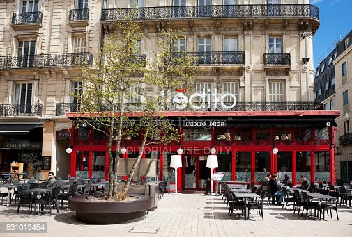 Dijon, France -- April 8, 2016: Facade of L'Edito cafe at Place Darcy in Dijon, France, people are sitting outside, having coffee, drinking.