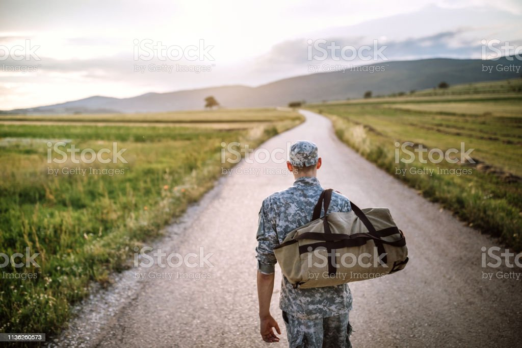Rear view of young soldier coming back home after war, carrying bag...