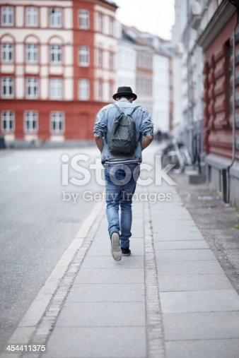 Rear view of a young guy walking down a city street