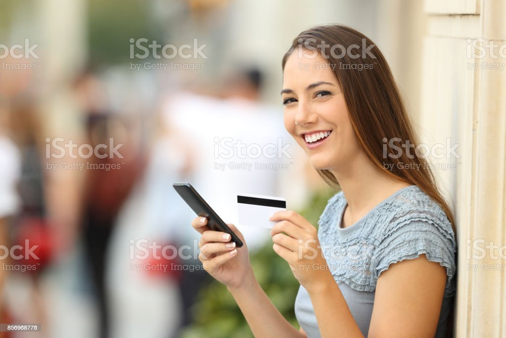 On line shopper looking at camera holding card - foto stock