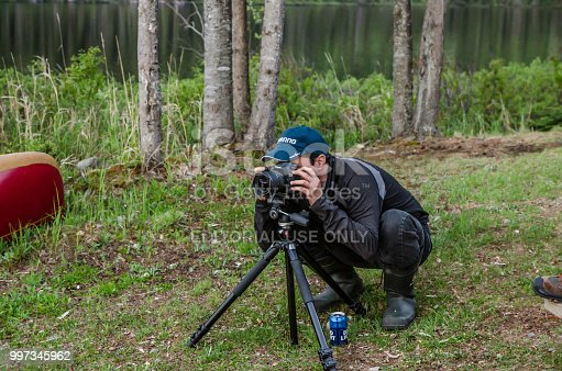 On man kneeling in front of camera and tripod to take a picture in nature at beginning of evening