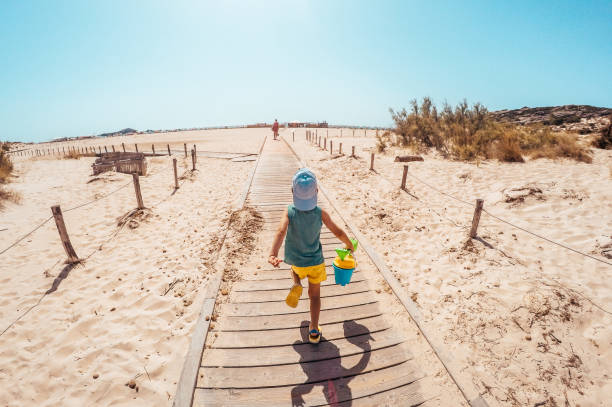 On my way to the beach Photo of a little boy holding his sand bucket during his walk on a boardwalk that leads to the beach boardwalk stock pictures, royalty-free photos & images