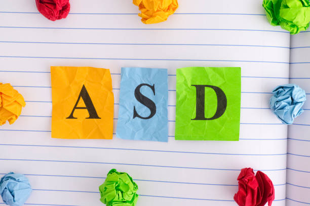 ASD (Autism spectrum disorder) on notebook sheet with some colorful crumpled paper balls around it stock photo