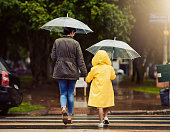 Rearview shot of an unrecognizable little boy and his mother holding hands and walking in the rain outside