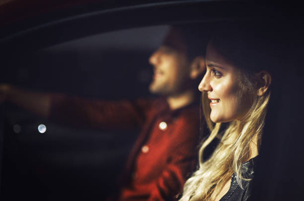 On our way to somewhere special Shot of a young couple traveling in a car together at night date night romance stock pictures, royalty-free photos & images