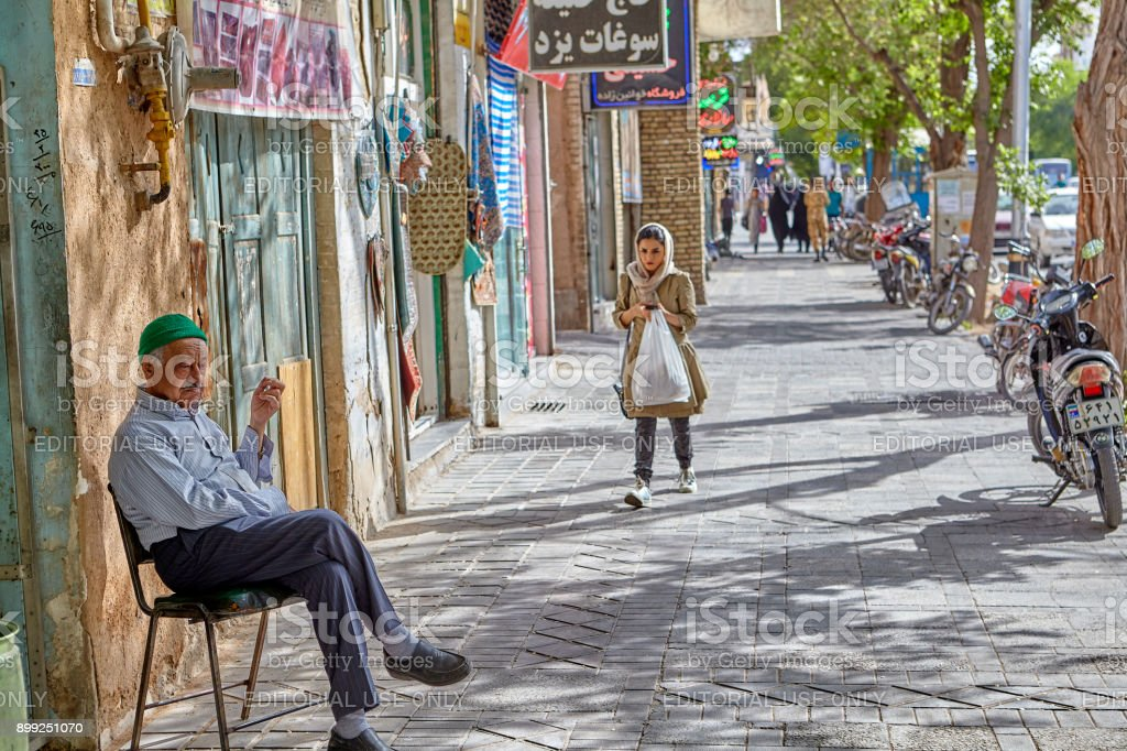On pavement there is chair in which old man sits. stock photo