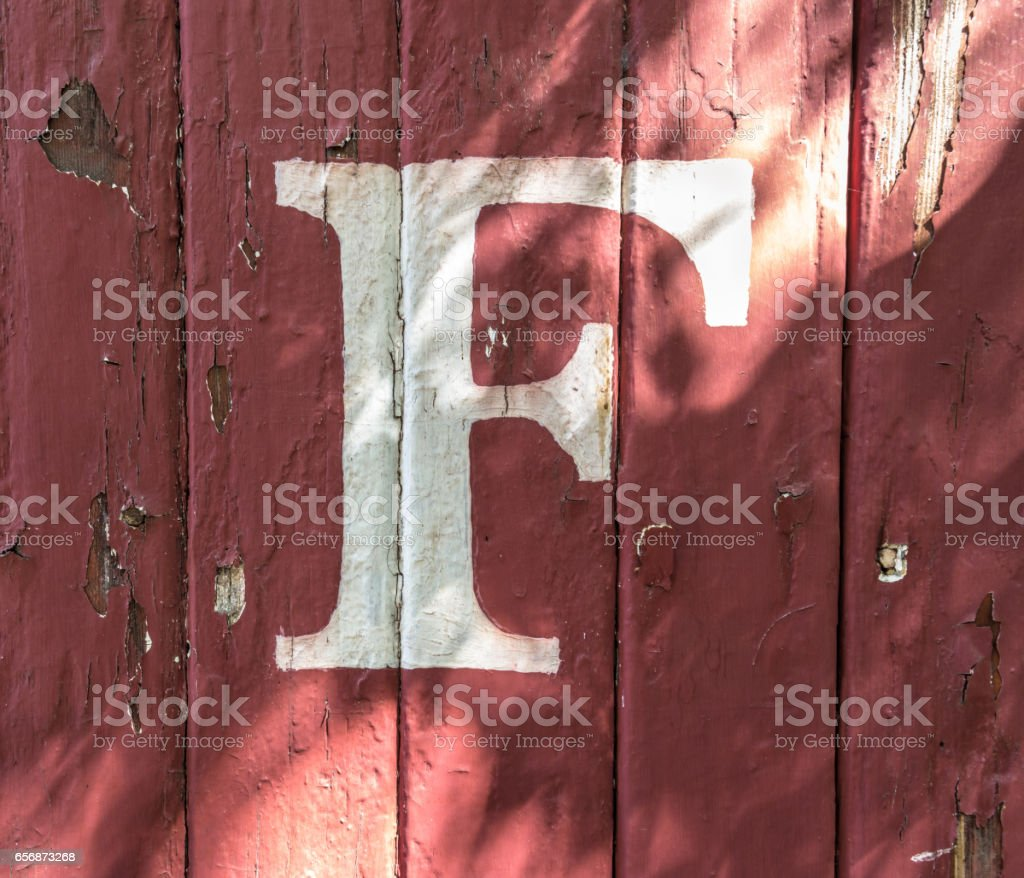 F on Red-Painted Wood Siding stock photo