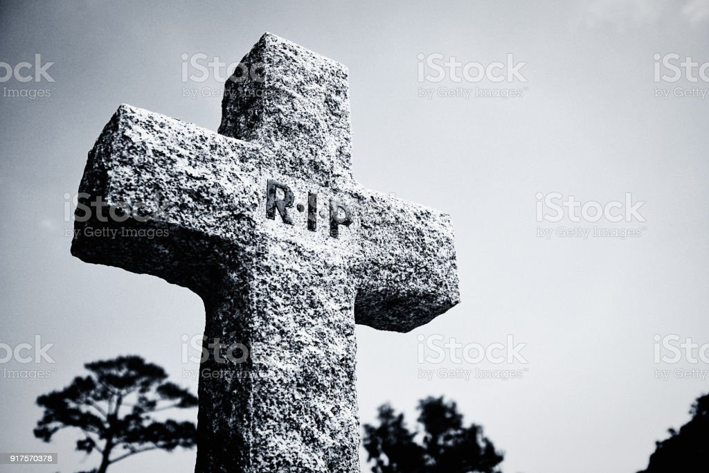 RIP on roughly carved stone cross in cemetery stock photo