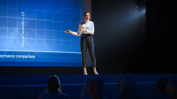 on stage: inspirational female speaker, talking about happiness, self, success, efficiency, health, and how to be more productive. tech industry business conference auditorium hall full off people - theatre full of people stage foto e immagini stock