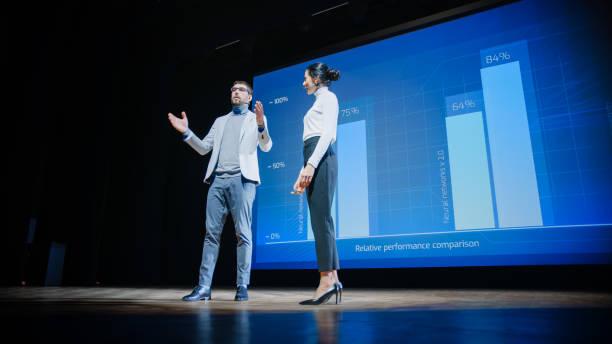 sul palco, ceo femminile di successo e relatori coo maschili presentano il nuovo prodotto dell'azienda, mostra infografiche, statistiche sul grande schermo, parlare di crescita. evento dal vivo, avvio tecnico, conferenza aziendale - evento foto e immagini stock