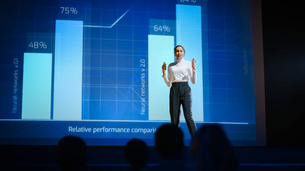 On Stage, Successful Female Speaker Presents Technological Product, Uses Remote Control for Presentation, Showing Infographics, Statistics Animation on Screen. Live Event / Device Release. stock photo