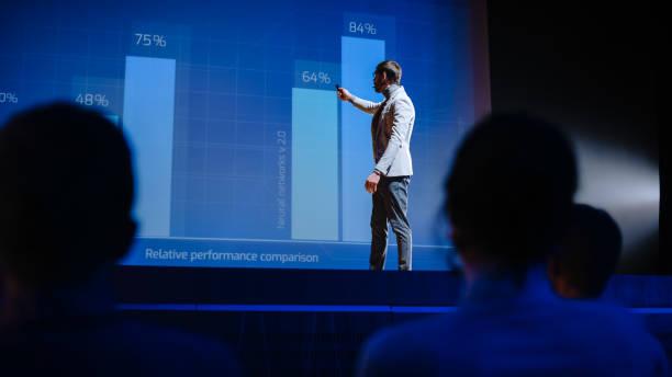 på scenen visionary male speaker presenterar ny teknik, använder fjärrkontroll för presentation, visar infographics, statistik animation på skärmen. live event / start-up business conference - graphs animation bildbanksfoton och bilder