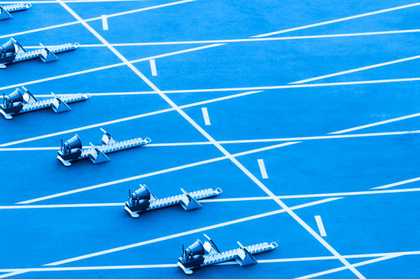 On starting block ready for sprint start.  Blue color filter On starting block ready for sprint start.  Blue color filter track starting block stock pictures, royalty-free photos & images