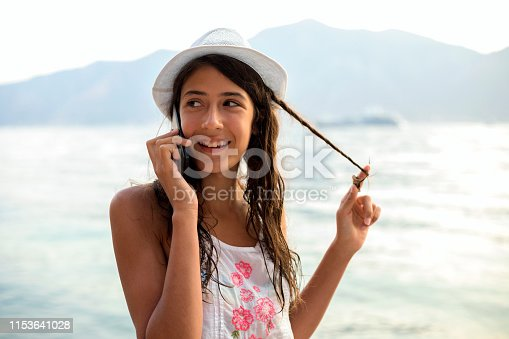 Happy teenage girl using mobile phone on the beach