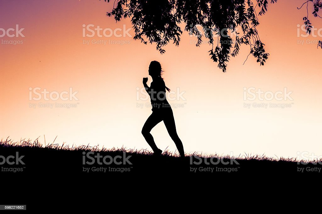 On sunset Silhouette of woman running outdoors - fitness training foto royalty-free