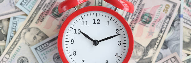 On table are American bills with red alarm clock. stock photo