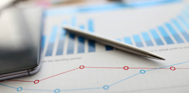 On table is report with graph and silver pen On table is report with graph and silver pen. Preliminary analysis target audience. Feature calculating interest on loan or deposit. Increasing sales, opening branches, creating franchise qualification round stock pictures, royalty-free photos & images