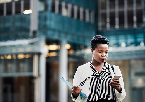 Shot of a young businesswoman using a mobile phone on the go in the city