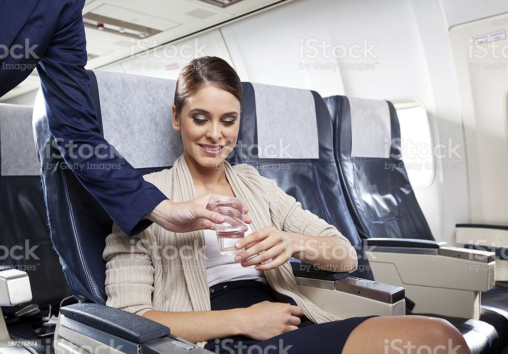 On the airplane Young woman sitting on the airplane and receiving a glass of water from air stewardess. 20-24 Years Stock Photo