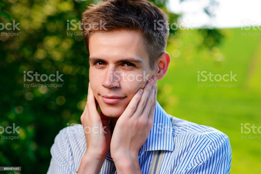 On the background of nature, a beautiful man looking into the camera holds his hands around his neck and face stock photo