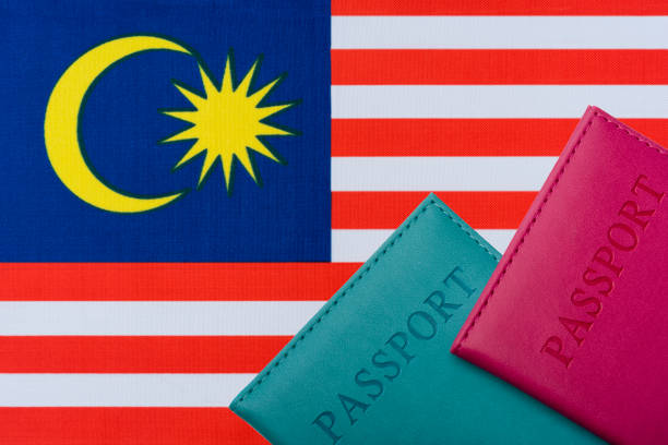 On the background of the flag of Malaysia two passports. On the background of the flag of Malaysia two passports. The concept of travel and tourism. pasport malaysia stock pictures, royalty-free photos & images
