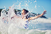 Small girl is jumping on the waves in the ocean