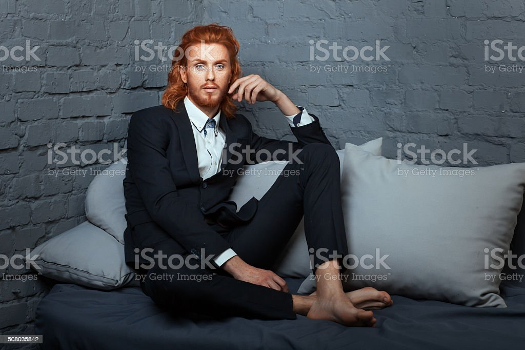 On the bed a man with freckles and red hair. stock photo