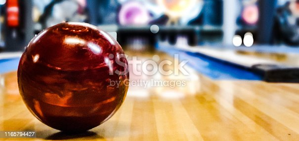 photo of a red bowling ball on the track taken in portrait.