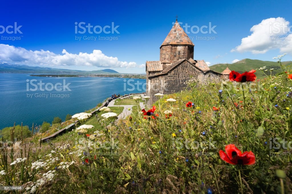 On the brink of rescue. The monastery on the mountain at the lake stock photo