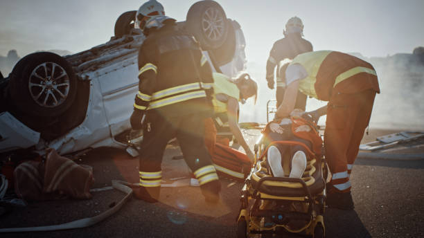 On the Car Crash Traffic Accident Scene: Rescue Team of Firefighters Pull Female Victim out of Rollover Vehicle, They Use Stretchers Carefully, Hand Her Over to Paramedics who Perform First Aid stock photo