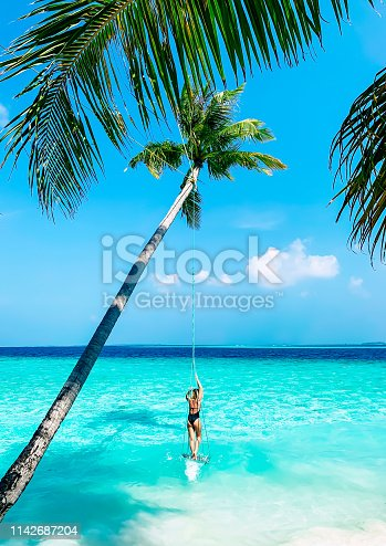 A vibrant green palm tree above a turquoise water of Maldives with a swing and a sporty girl in a black swimsuit staying on it.