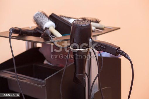 696318954 istock photo On the Desk of the hairdresser are Hairdryers, combs, Curling irons and straighteners close up 690532916