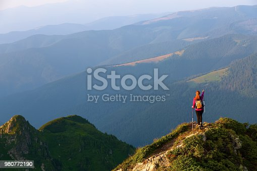 On the edge of the abyss on the lawn among the landscapes with high mountains and fields there is a tourist with a backpack and trekking sticks, and indicates the path.