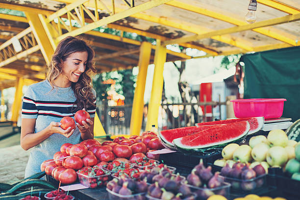 On the farmer's market Smiling woman choosing fruits and vegetables on the farmer's market. farmer's market stock pictures, royalty-free photos & images