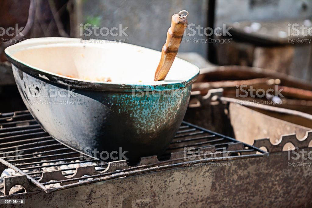 on the grill stands a cauldron in which to prepare meat and vegetables foto stock royalty-free