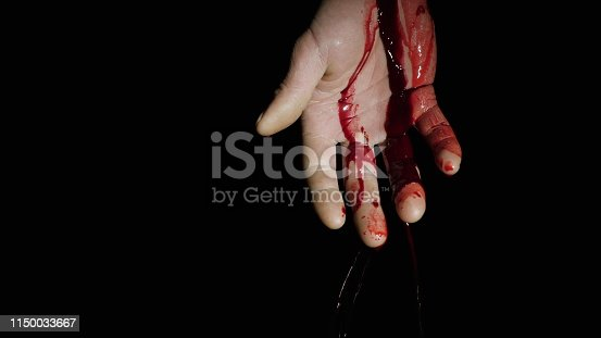 On the human hand, natural blood flows down against a dark background. Close-up