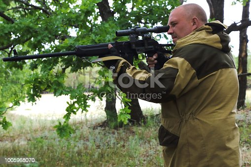 On the hunt. A man of 35-40 years old, a military hunter aiming from a firearm in the forest.