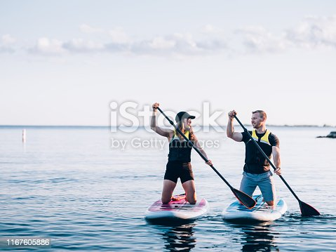 Millennial couple Paddle boarding on Lake Ontario in the evening.
