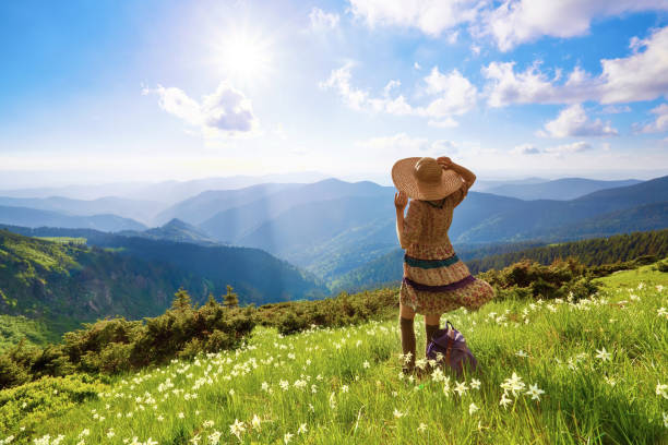 On the lawn in mountains landscapes the hipster girl in dress, stockings and straw hat stays watching the sky with clouds. Beautiful spring scenery. On the lawn in mountains landscapes the hipster girl in dress, stockings and straw hat stays watching the sky with clouds. Beautiful spring scenery. sun shining through dresses stock pictures, royalty-free photos & images