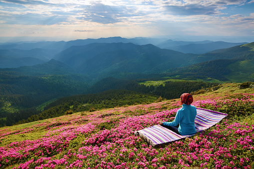 On the lawn in pink rhododendrons the girl is sitting in lotus posture on the striped rug. Meditation at the high mountains and sky with rays and clouds. Beautiful spring day.