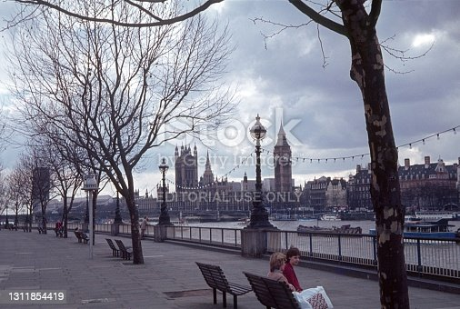 London, England, UK, 1979. Promenade on the River Thames. In the background: Big Ben and the Westminster Parliament building. Also: local.